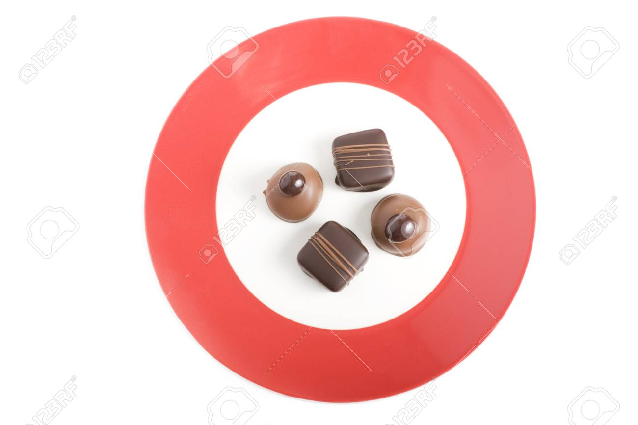 Four Gourmet Chocolates on Red Rimmed Plate.  The shot is studio isolated on a white background Stock Photo - 7471496