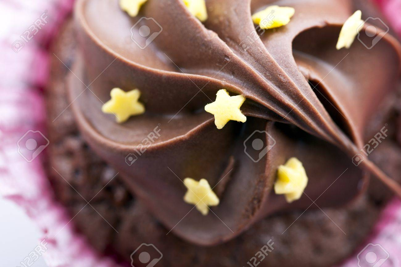 Close-up of chocolate cupcake frosting with yellow stars.   Angle from directly above. Stock Photo - 11806625