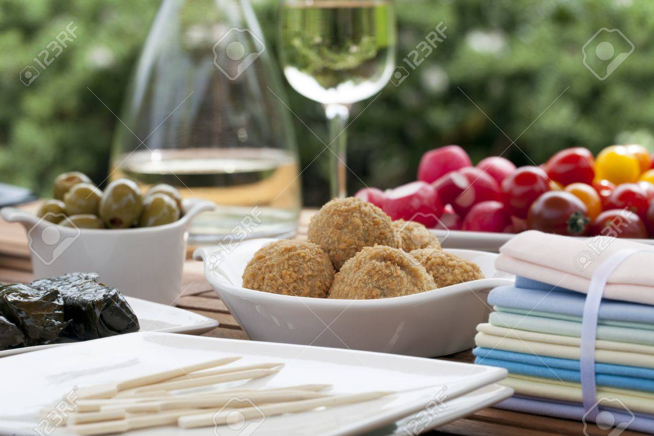 Summer tapas table with bitterballen in focus, and wine, olives and radishes in the background Stock Photo - 14157985
