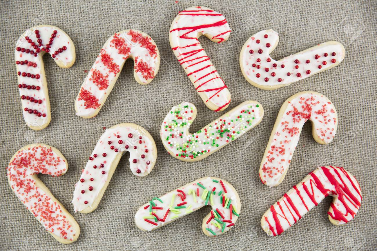 Candy Cane Shaped Sugar Cookies With Frosting And Sprinkles On