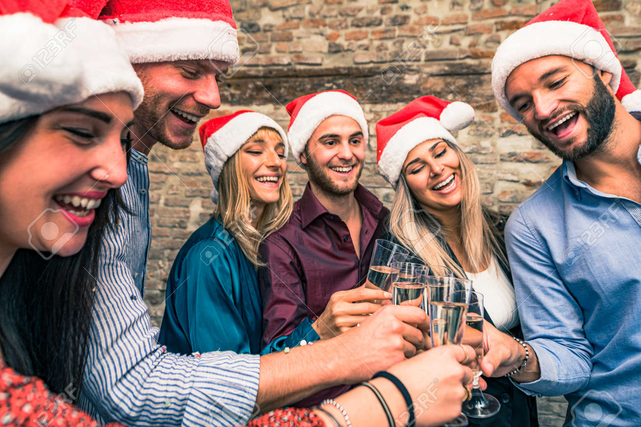 Merry Christmas and Happy New Year! Young freinds are celebrating holidays in hause - Group of young entrepreneurs are drinking champagne in coworking, wearing xmas cap - Lifestyle concept - 159198547