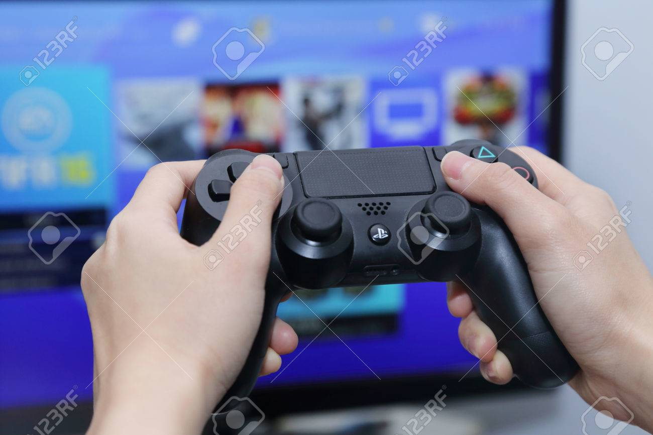 Thailand October 2 Hand Playing Sony Dualshock 4 Controller Ds4 New Dual Shock Light Blue Model Stock Photo For Playstation With The Screen On Background Taken In Bangkok