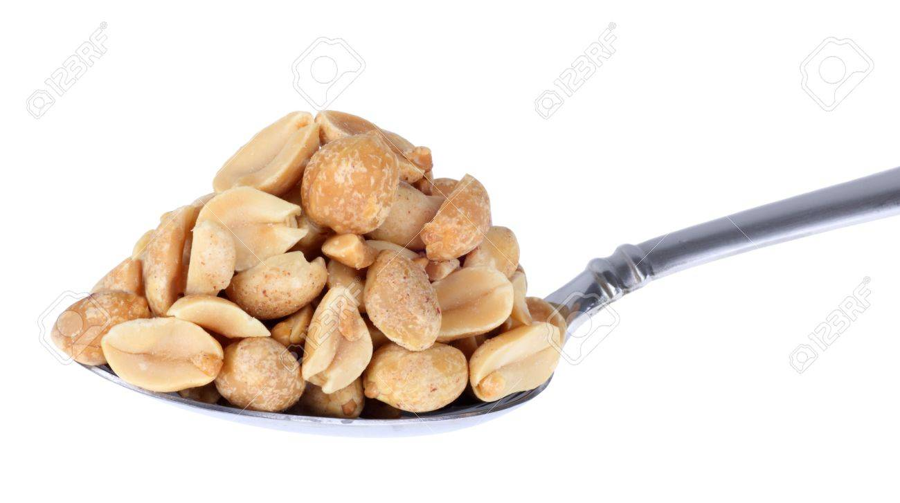 heaping pile of peanuts on a spoon isolated on white stock photo