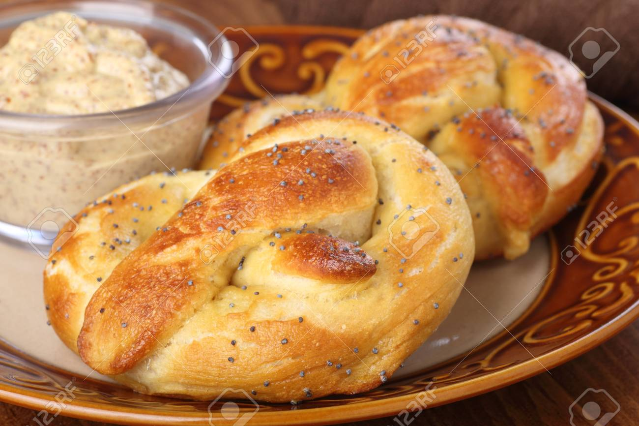 Closeup of two soft pretzels with mustard dip on a plate Stock Photo - 17717007