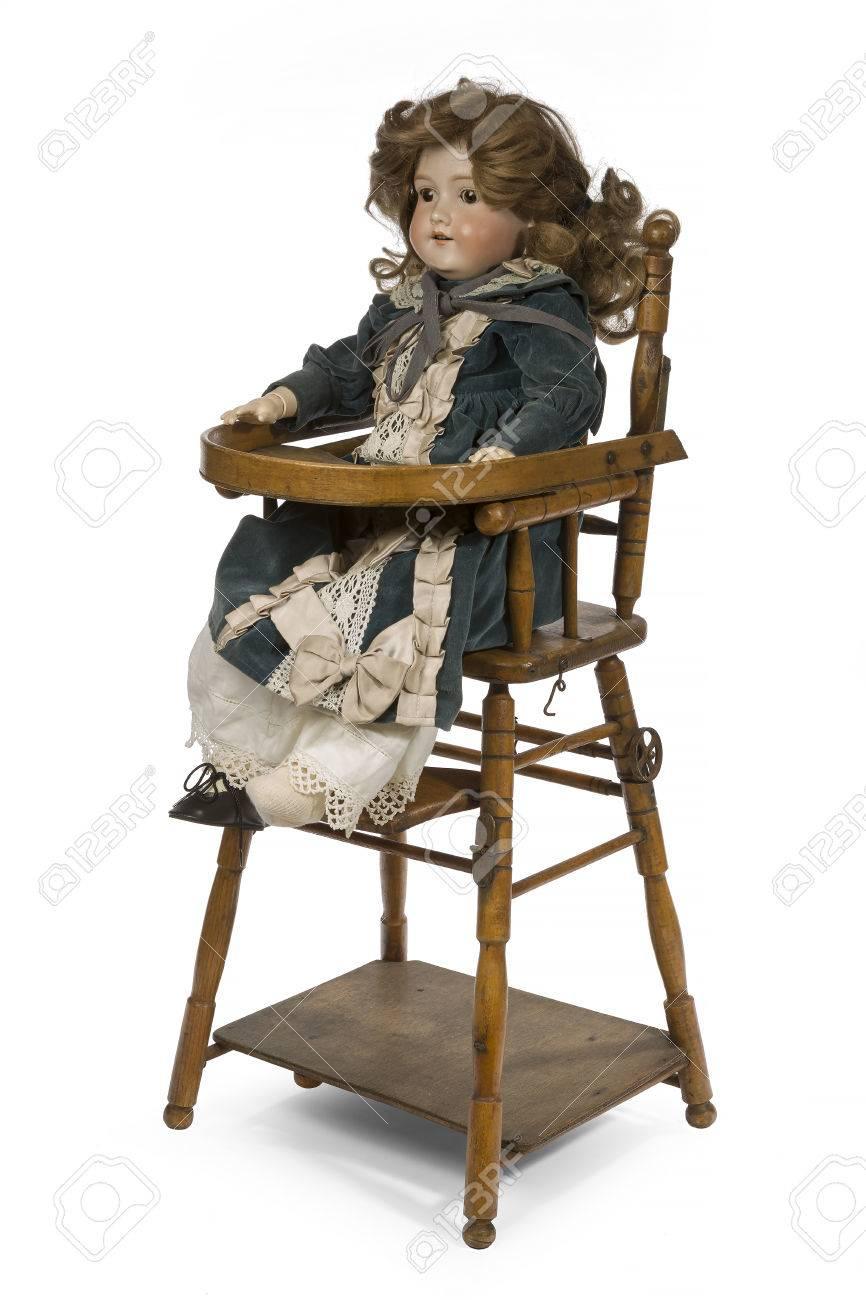 Grande poupée en céramique allemande impressionné Am articulée et habillée  de velours dans une chaise haute pour enfant.