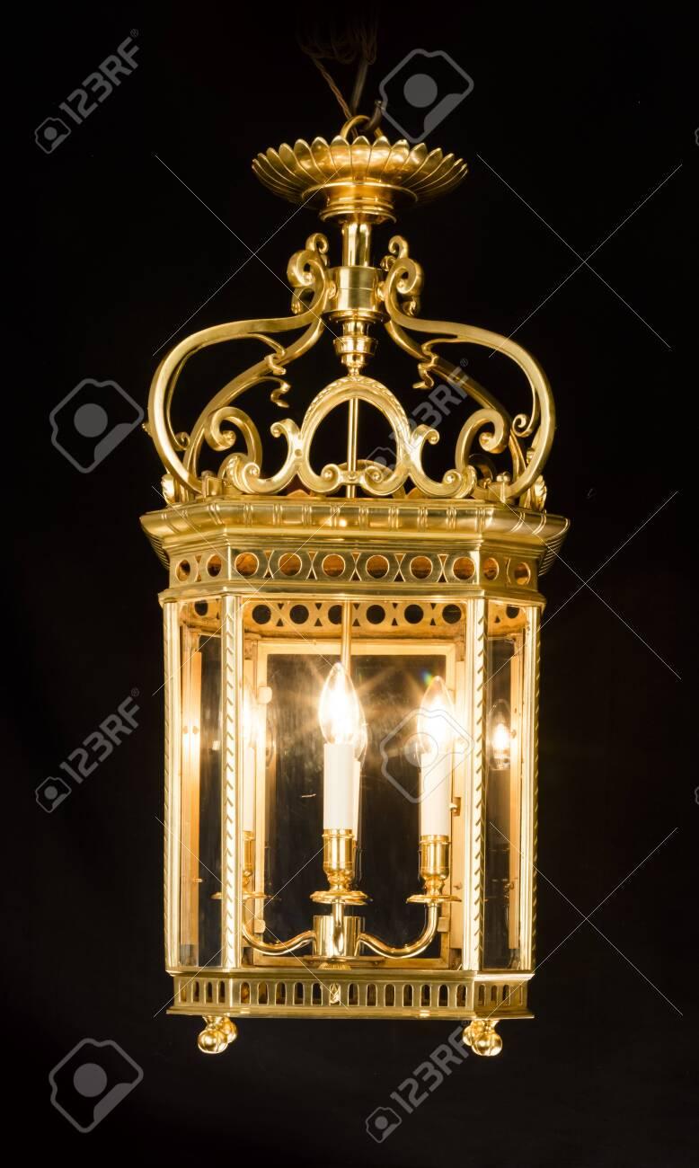 Antique decorative hanging electric brass hall lantern light illuminated glowing isolated on black - 131722114