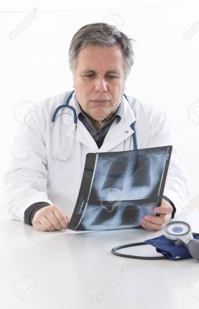 mature doctor examining an x-ray stock photo, picture and royalty