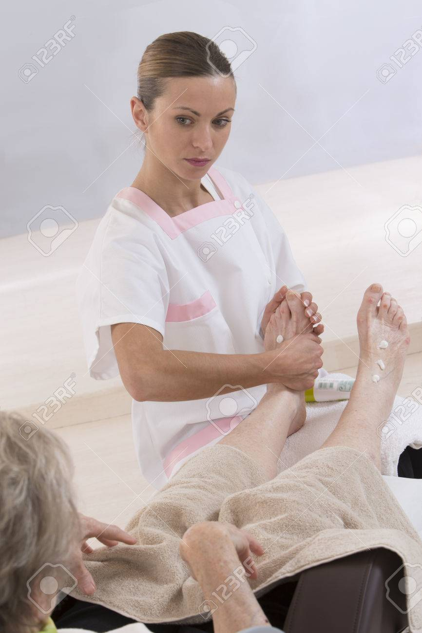 Nurse or care giver massaging foot of an elderly woman