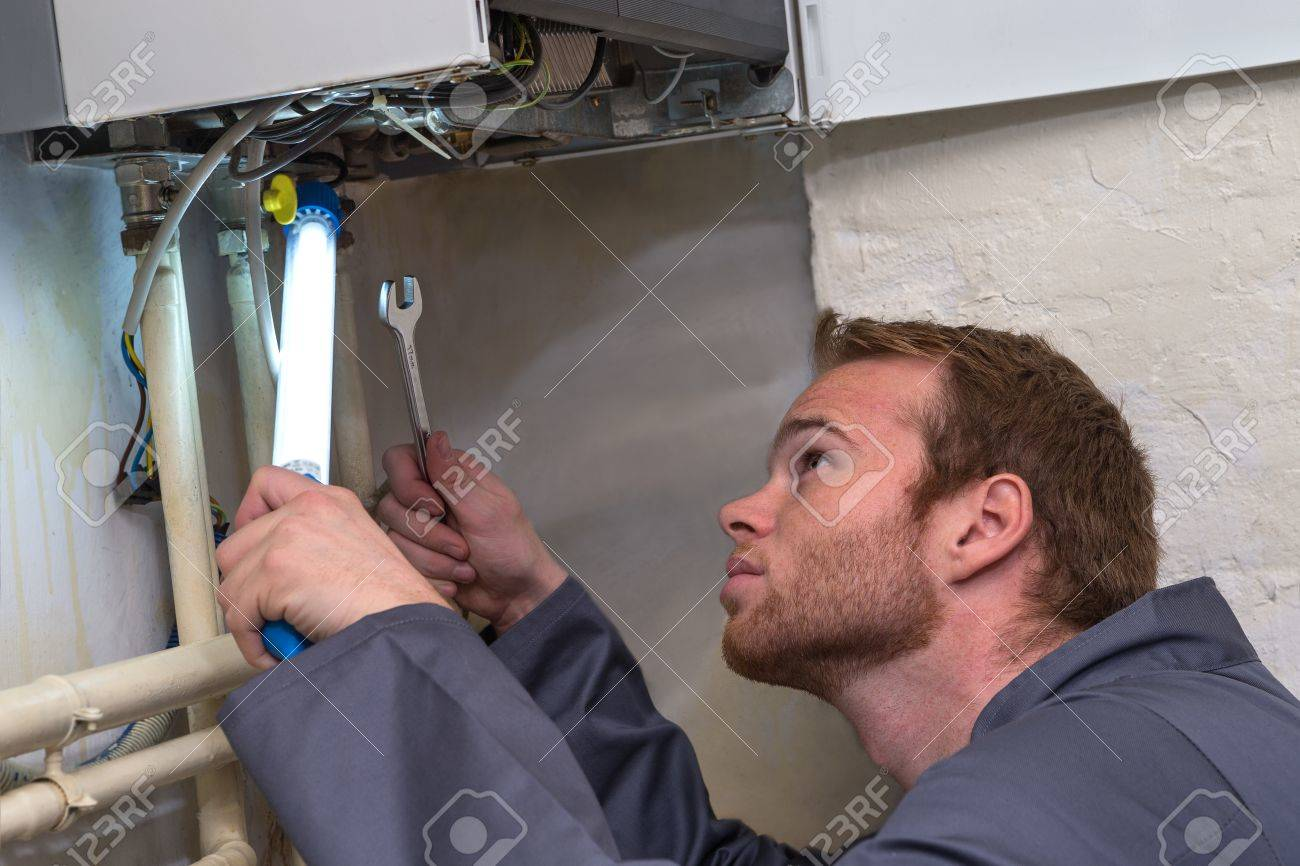 Engineer controlling the heating pipes at the boiler room - 50347483