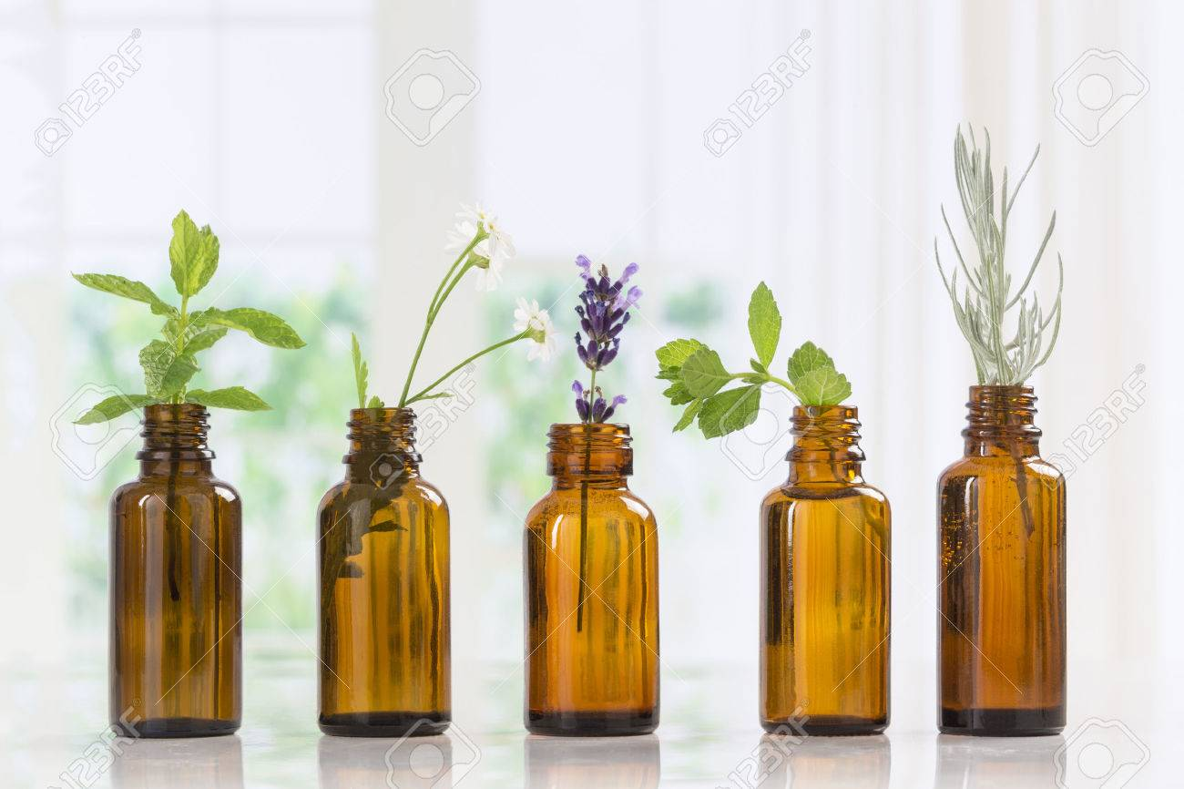 Bottle of essential oil with herbs and spices in brown bottles - 60587330