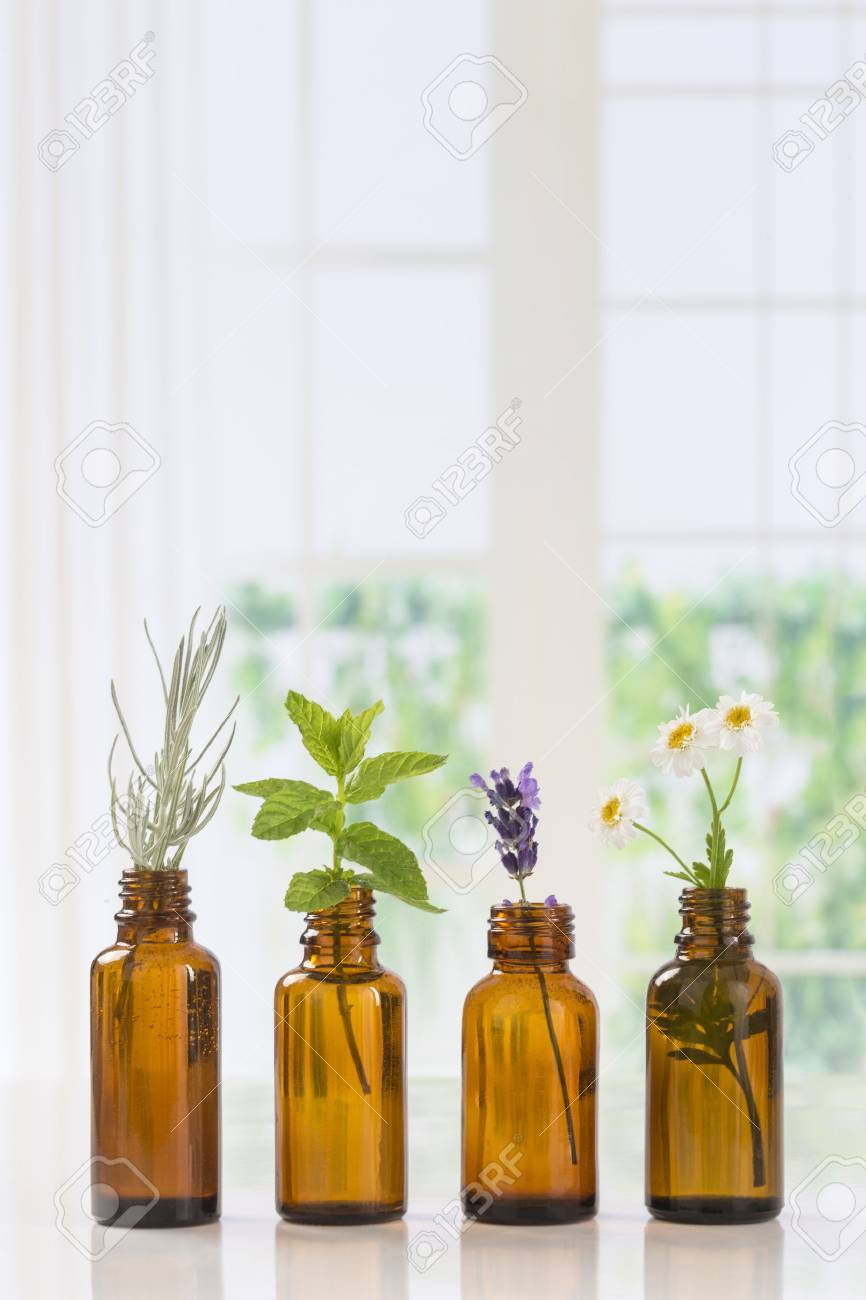 Bottle of essential oil with herbs and spices in brown bottles - 60587262