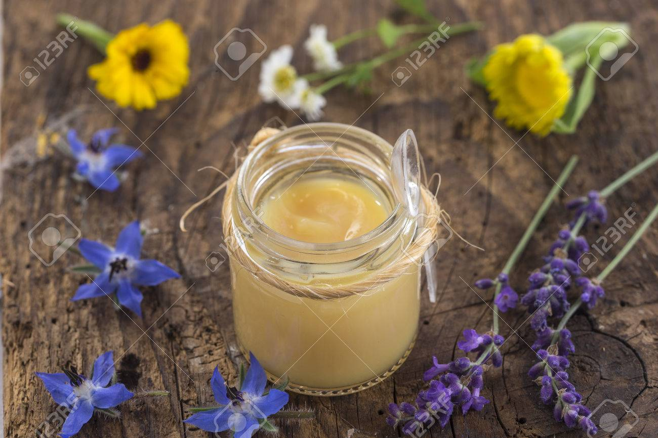 raw organic royal jelly in a small bottle on s wooden board - 63674260