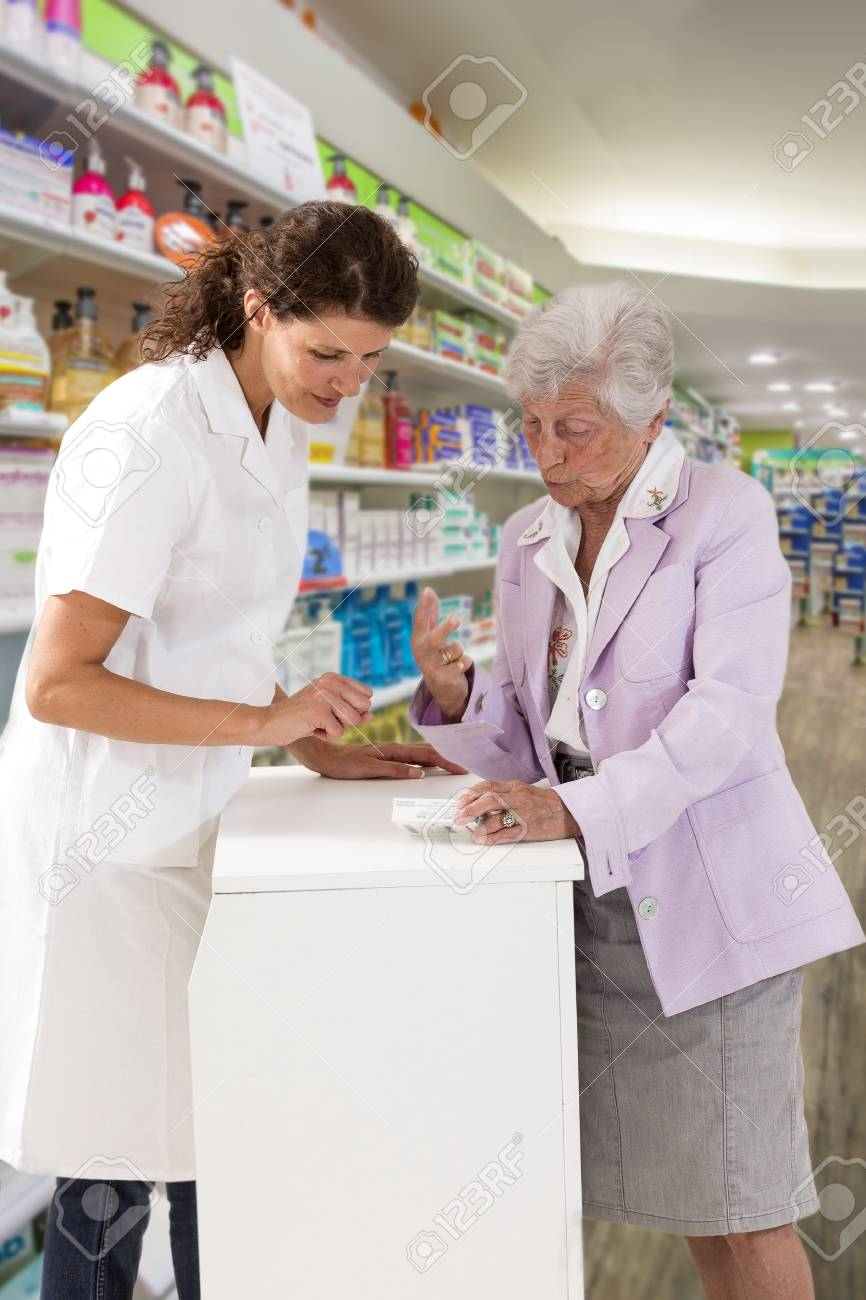 medicine, pharmaceutics, health care and people concept - happy pharmacist showing drug lnstruction to senior woman customer at drugstore - 98108608