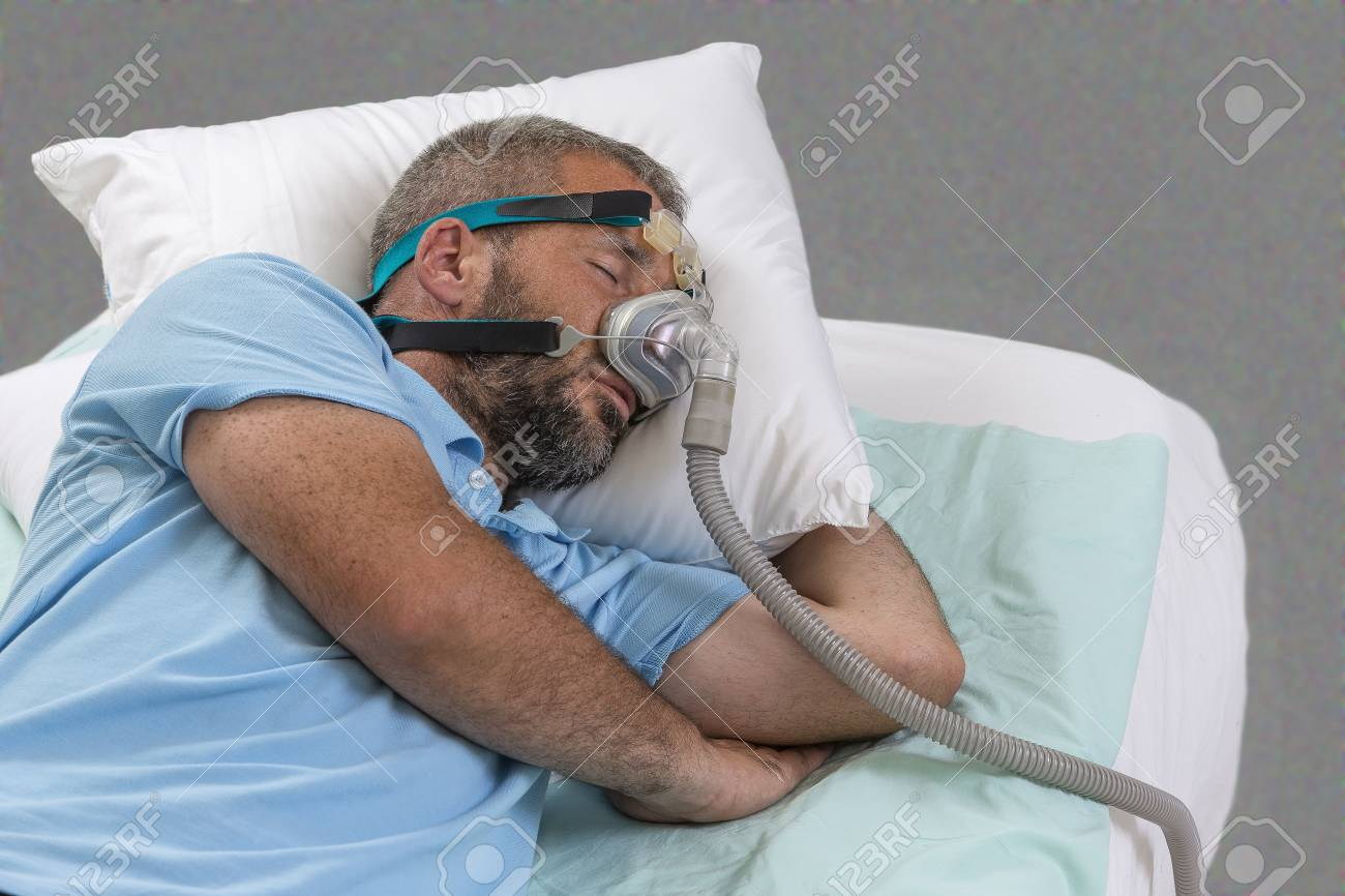 Man with sleeping apnea and CPAP machine on grey