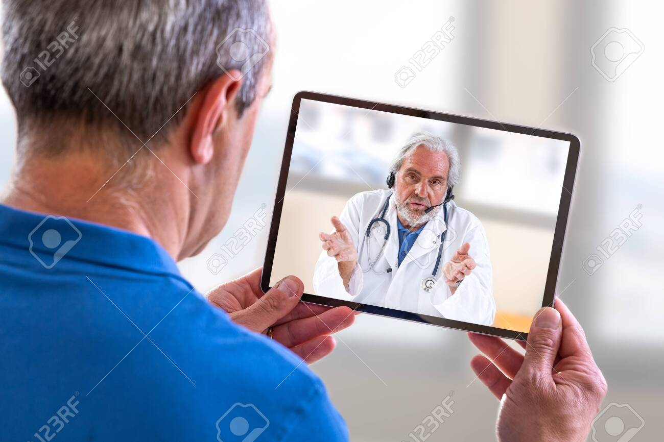 Telemedicine concept, Doctor sitting at hospital, with laptop, having an online call with a patient showing a ablet device - 127667145