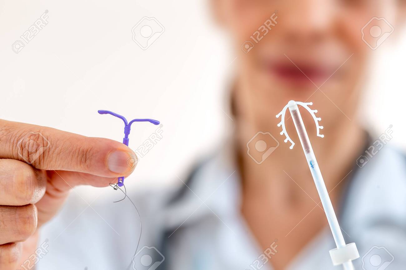 Female doctor holding two knd of intra utreine devine for birth control IUD - 129576998