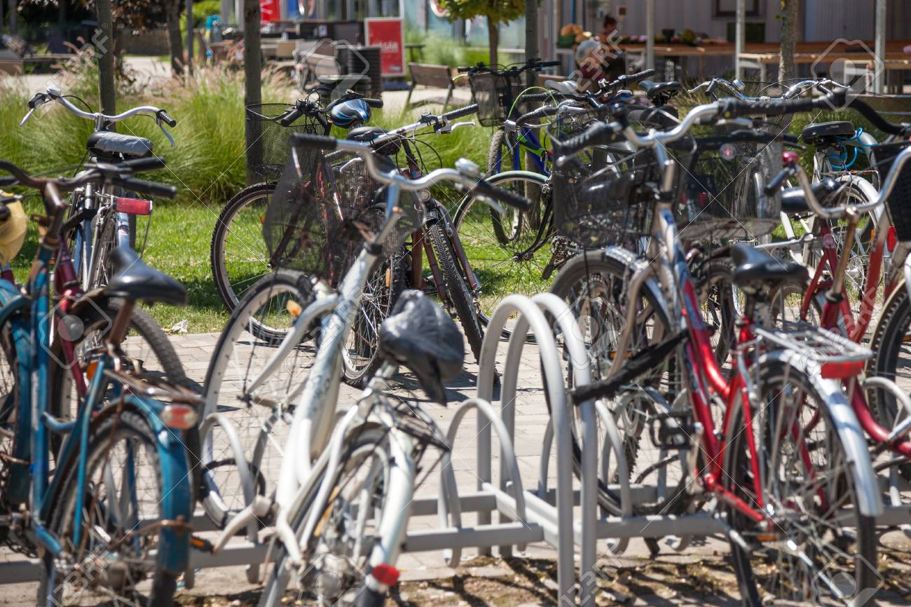 SZEGED, HUNGARY - JUNE 3, 2018: Bicycles raks full of bikes parked by communters near the Szeged market. Hungary is famous for his huge use of bicycle as a transportationPicture of a bike parking lot crowded with bicycles stuffed on racks, during a warm - 111319959