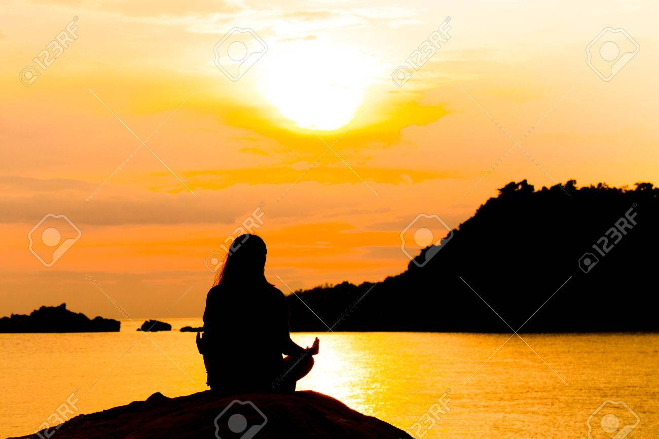 Silhouette Woman Meditating In Yoga Pose Or Lotus Position By The Sea At Sunset