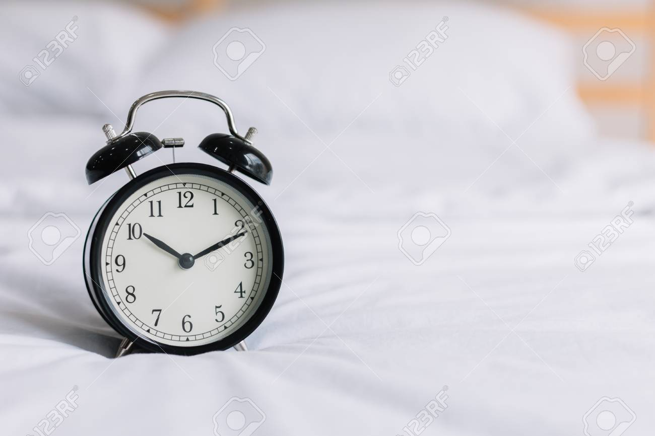 Retro Alarm Clock On Bed In Bedroom At Morning. Use For Alarm To Wake Up