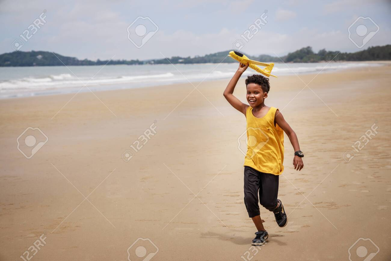 Happy colored boy and African American boy playing yellow toy airplane and running by wearing yellow sweater. Having fun on beach after unlock down city from COVID19. concept of dreams and travels - 148183502