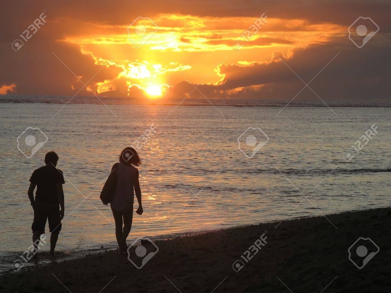 Happy couple walking in the sunset at Mauritius beach - 15416355