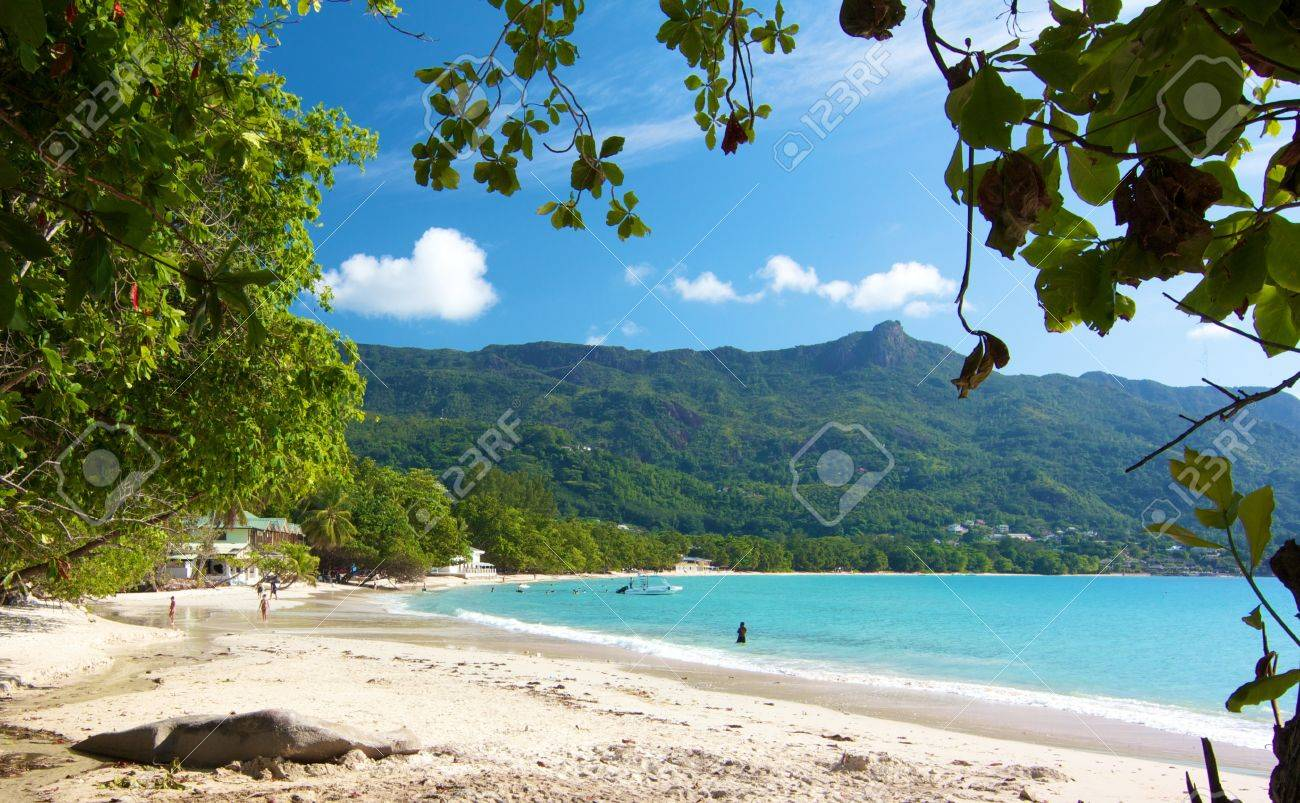 View over the amazing Beau Vallon bay with a few people walkingalong the white beach on Mahe island, Seychelles - 15450952