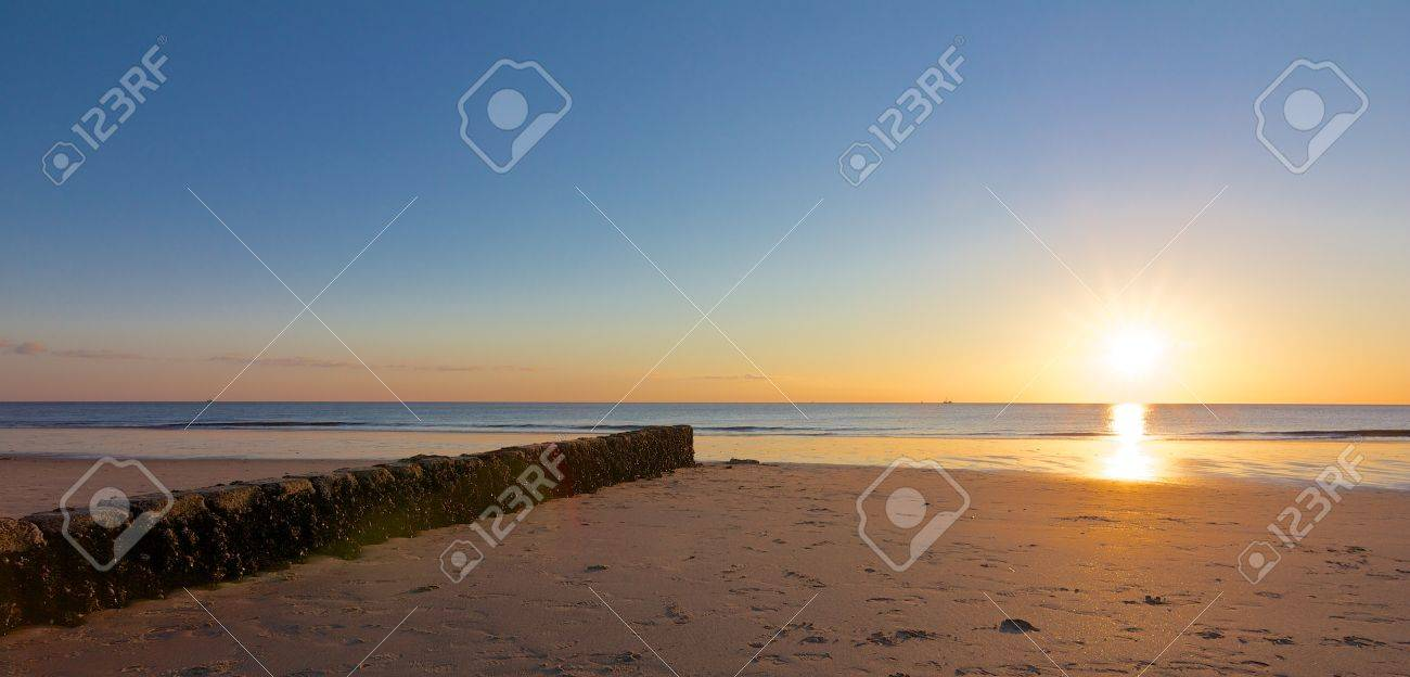 Rock groin leading towards a beautiful sunset on a lonely North Sea beach - 19903574
