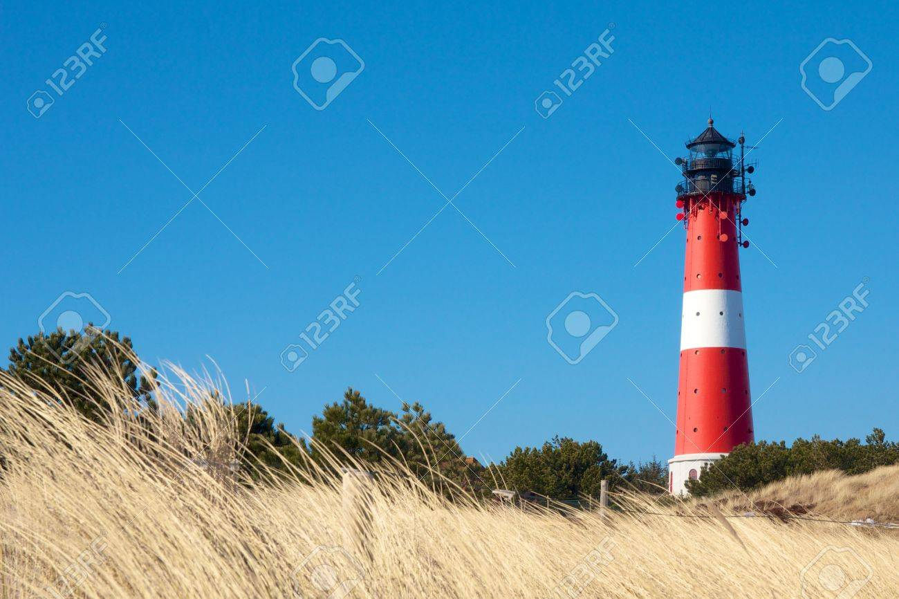 Small lighthouse against a clear blue sky with a dune full of beach grass - 21014943