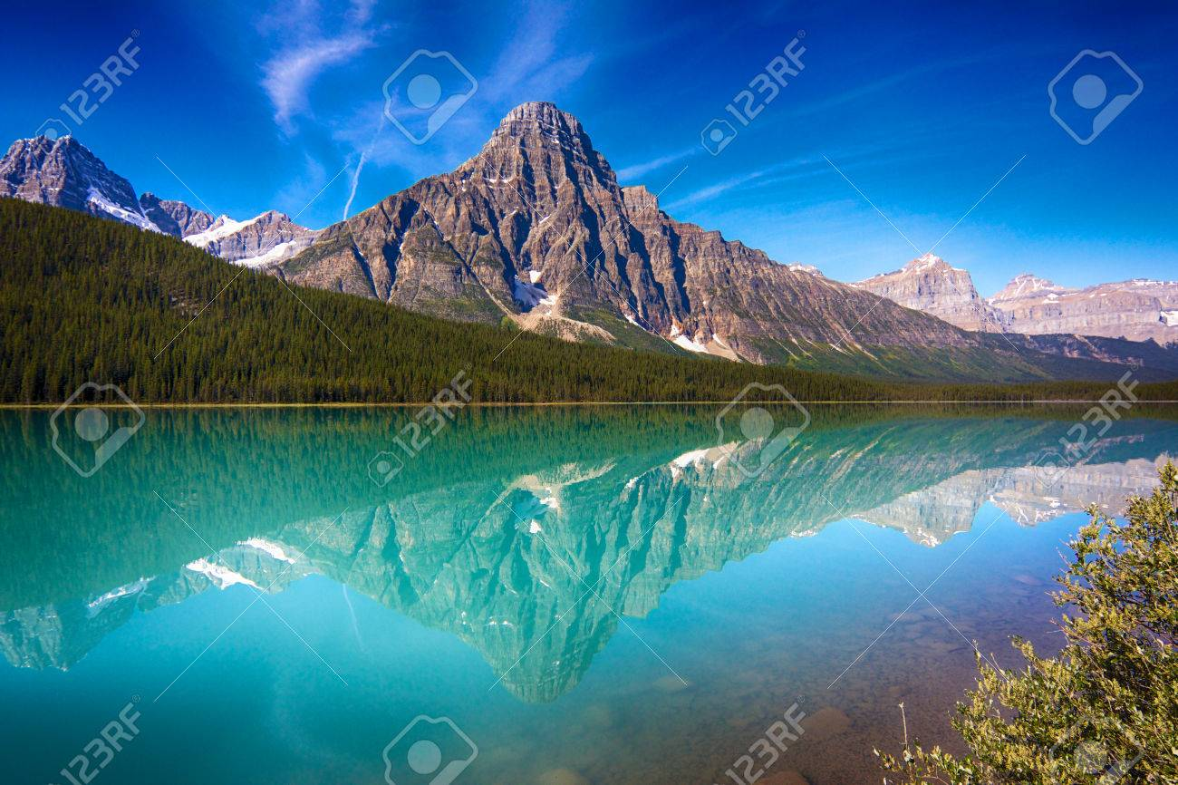 View on Hector Lake with a mountain reflecting in the quiet waters - 23693132