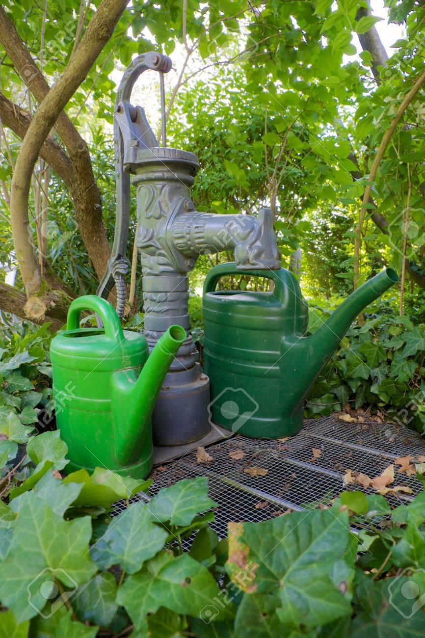 traditionelle pumpe gut mit twi grünen gießkannen in einem grünen