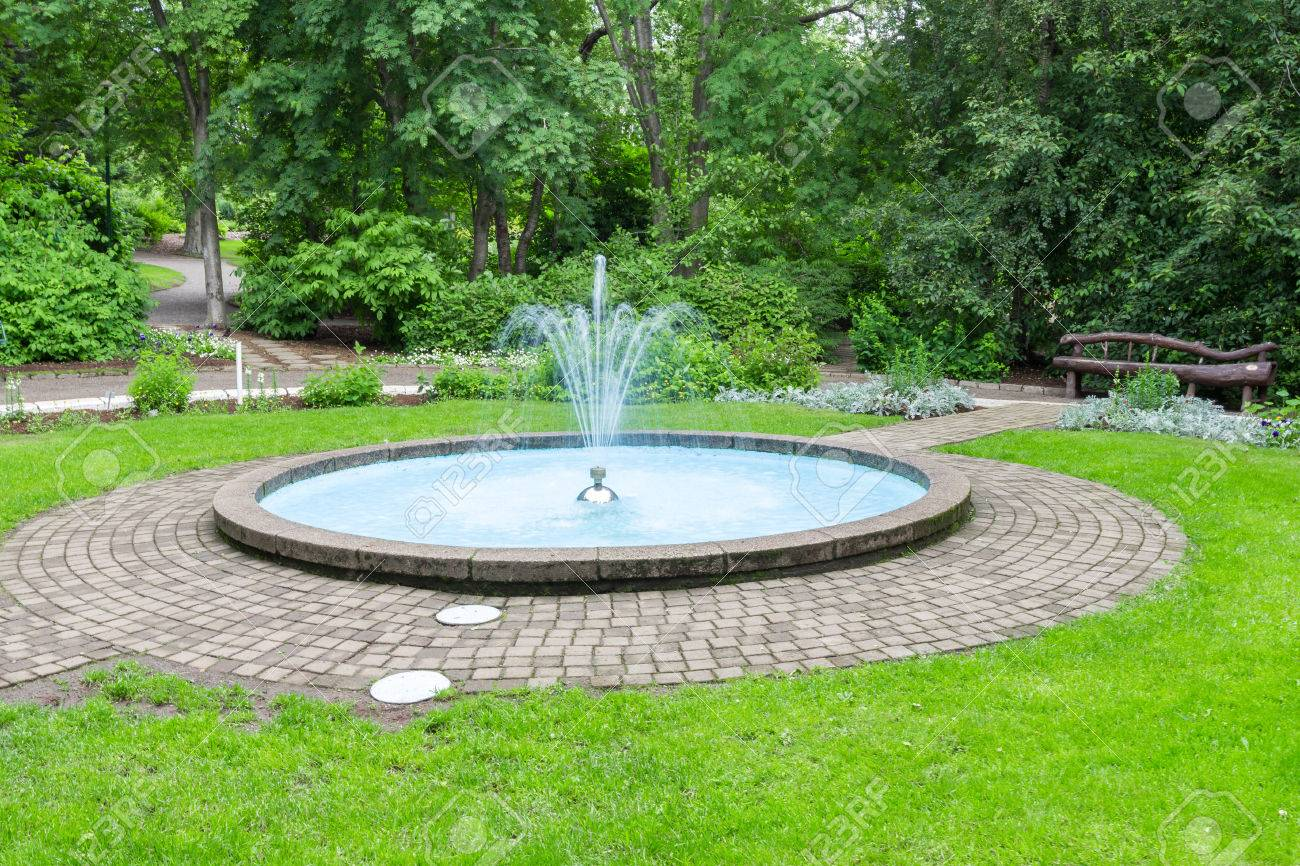 Small fountain and pool in a park with grass and trees around it - 80031030