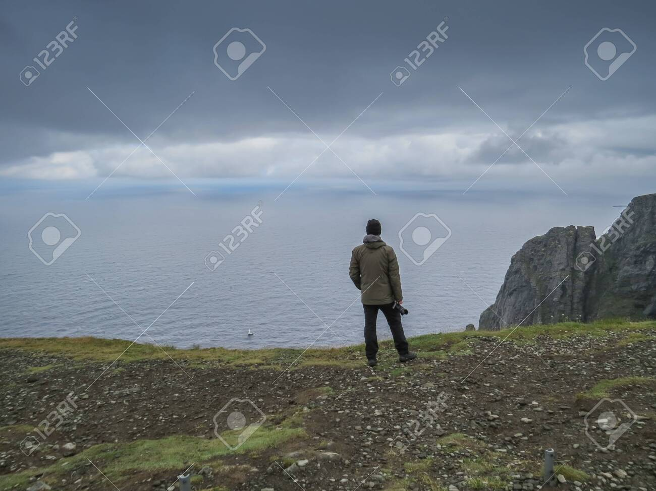 Lonely photographer standing at a rock cliff high above the arctic sea at North Cape, Norway - 134623330