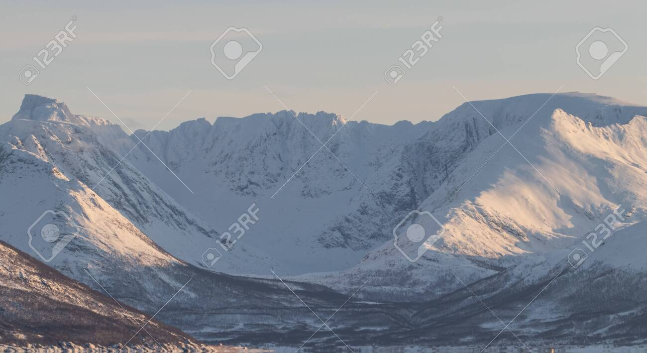 Epic Norwegian fjord and barren, snow covered mountains during sunset, far above the polar circle near Skjervoy - 134623331