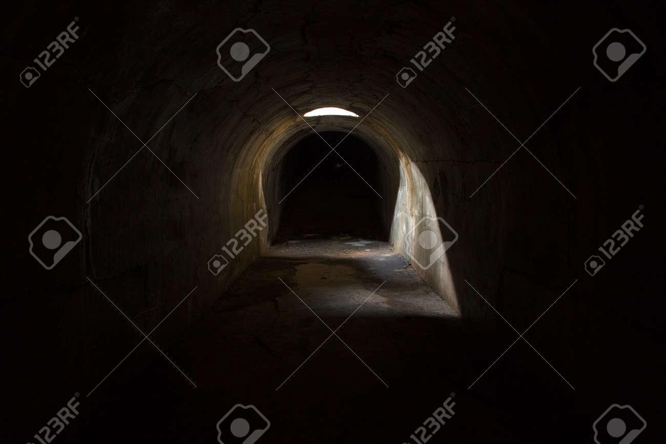 A gloomy dark underground corridor, sealed through a hole in the ceiling at Fort Pospelova on the Russian island in Vladivostok. - 154333866