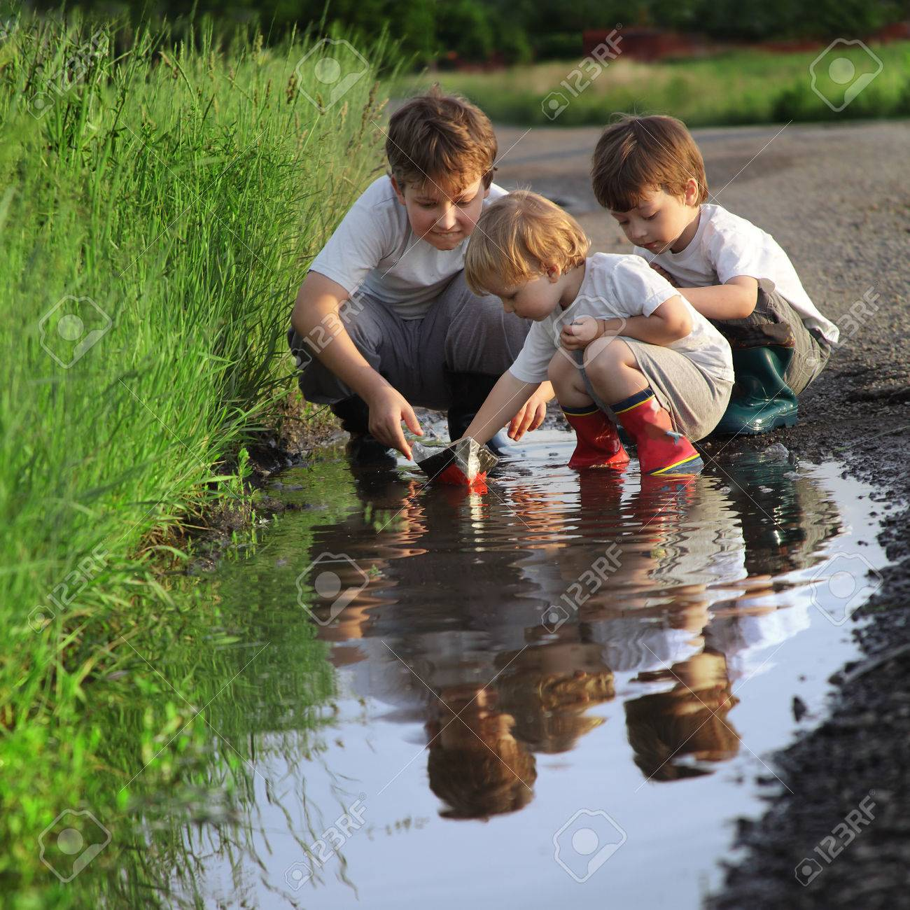 three boy play in puddle - 26035363
