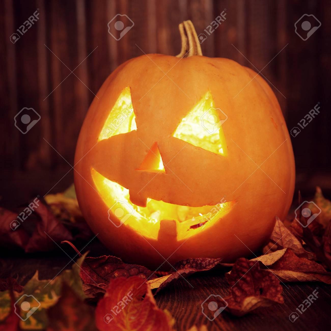 Facce Zucche Di Halloween.Faccia Di Zucca Jack O Lanterne Di Halloween Su Priorita Bassa E L Autunno In Legno Foglie