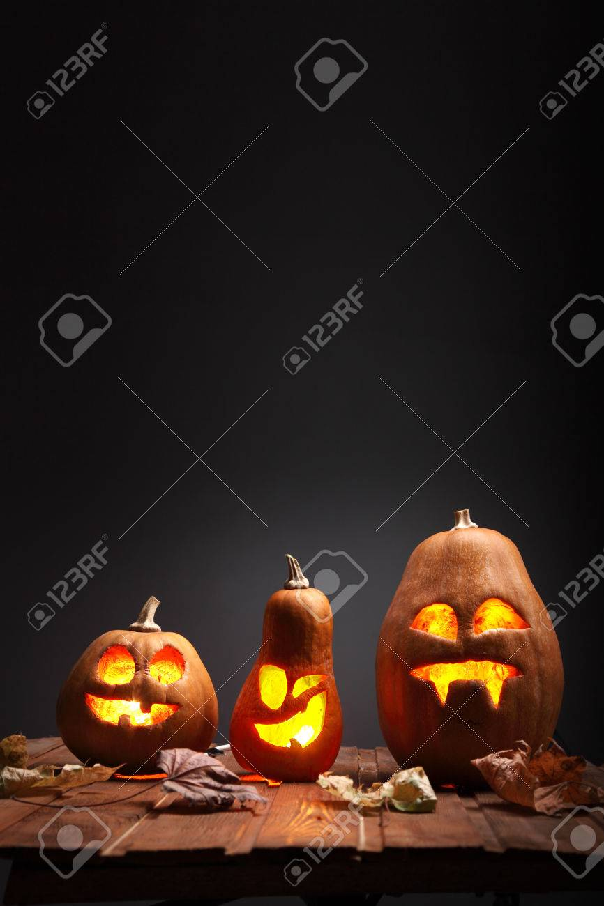 Jack o lanterns Halloween pumpkin face on wooden background and autumn leafs - 45522823