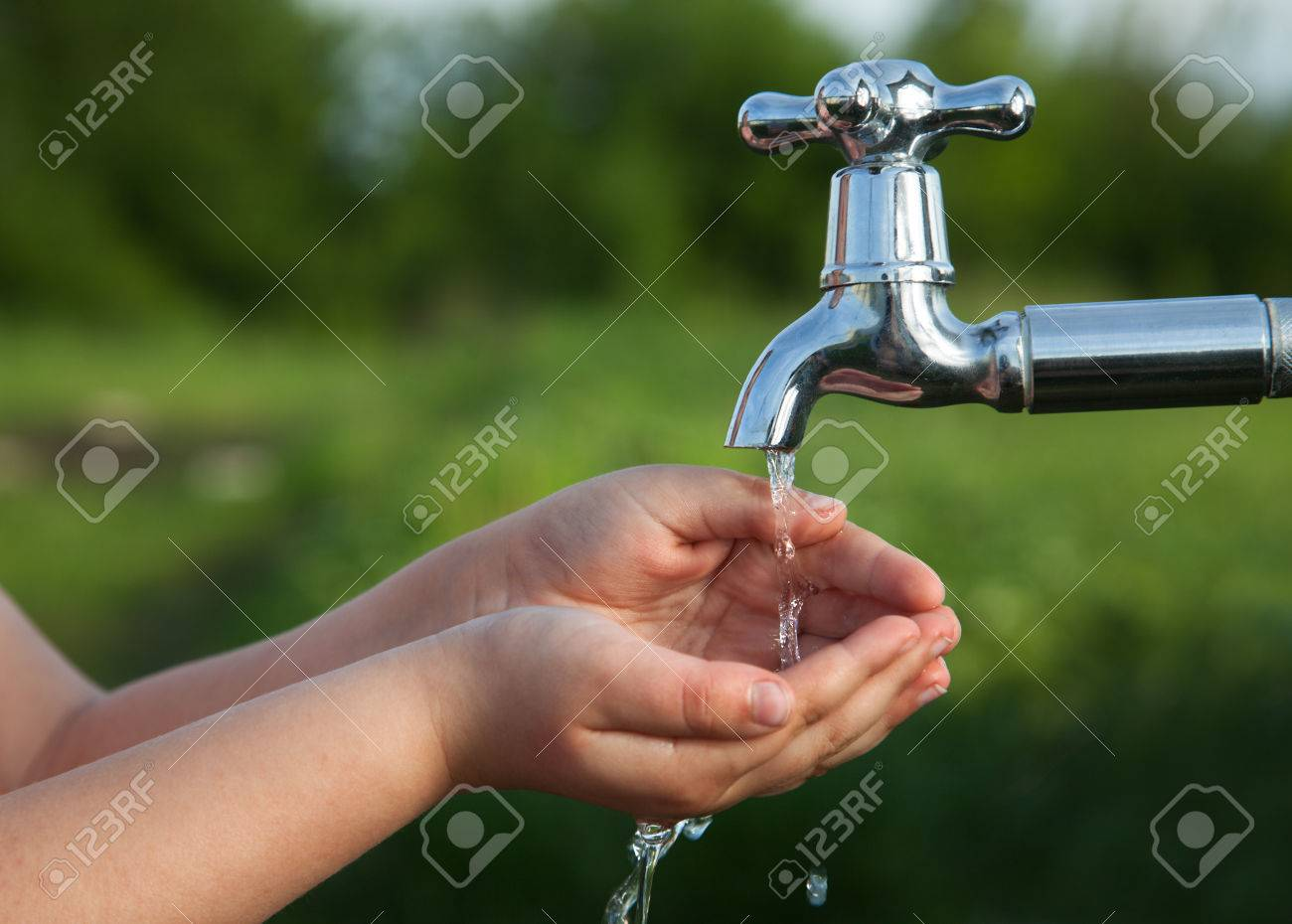 boy washes his hand under the faucet in the garden - 58843692