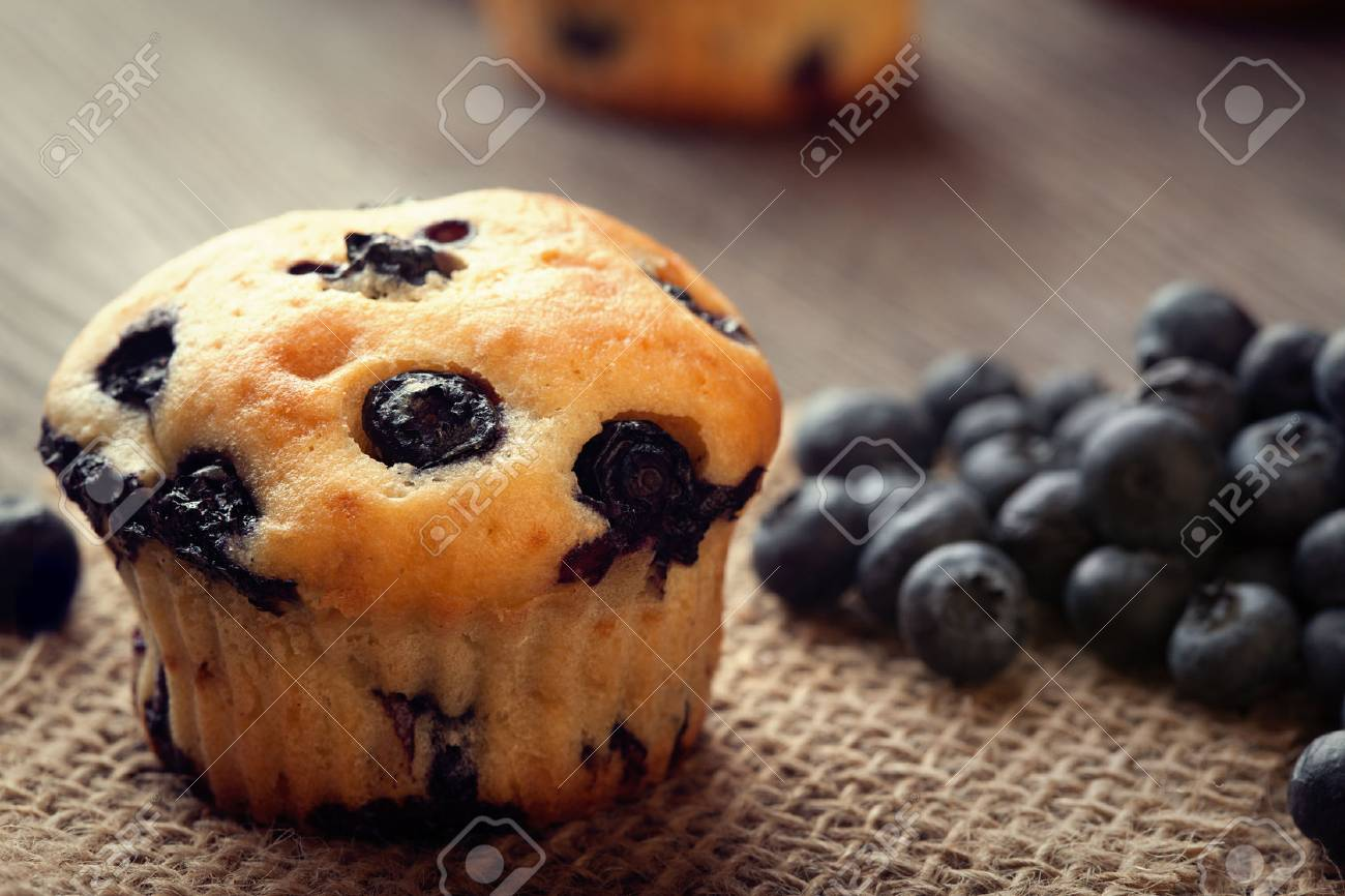 muffin with blueberries on a wooden table. fresh berries and sweet pastries on the board - 65174987