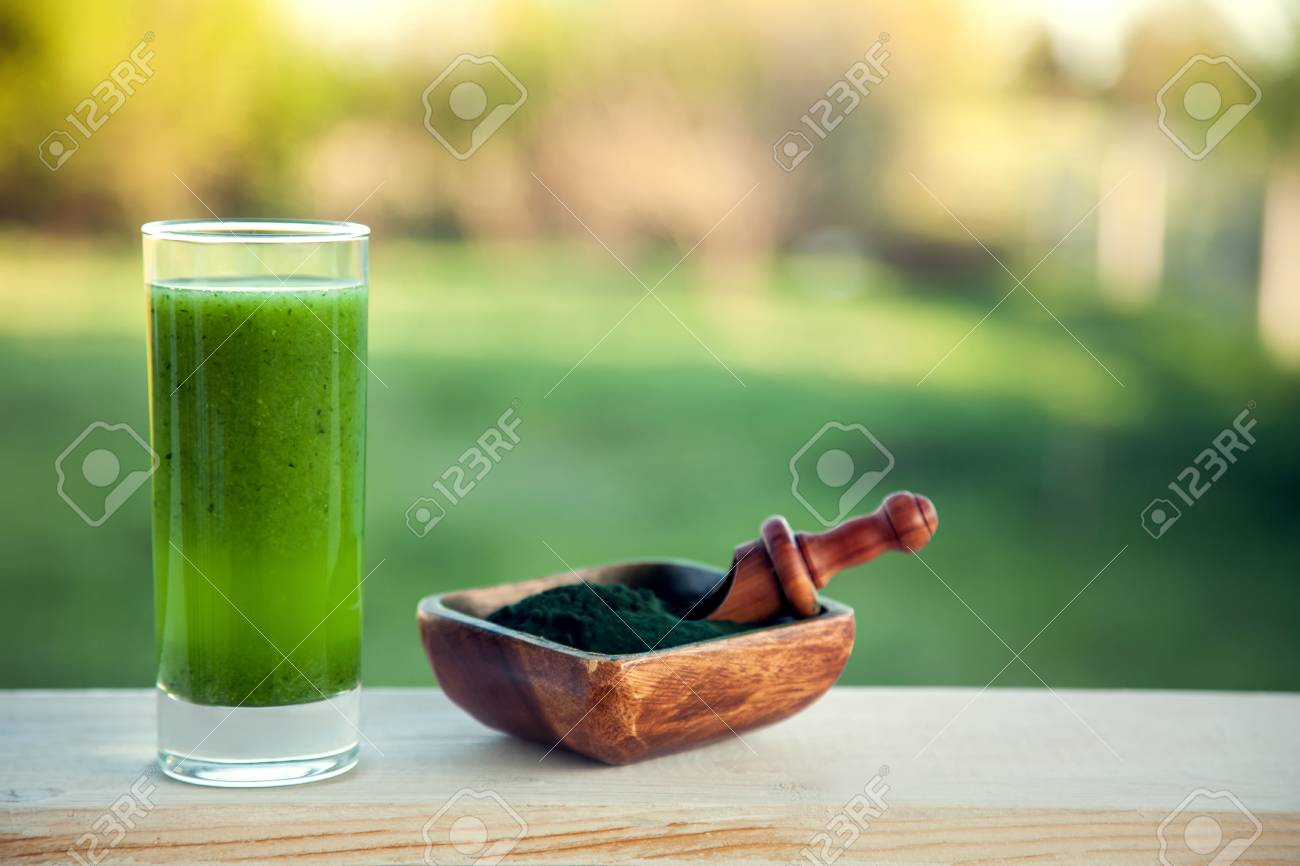Green smoothie with spirulina on wood background - 96400228