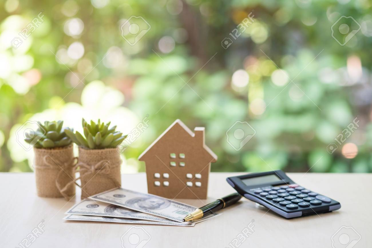 Home Loan, mortgage and real estate concept, House model with pile of dollar bills, calculator, pen and plant pots on table with garden background for business, finance, banking, and saving money. - 100807989