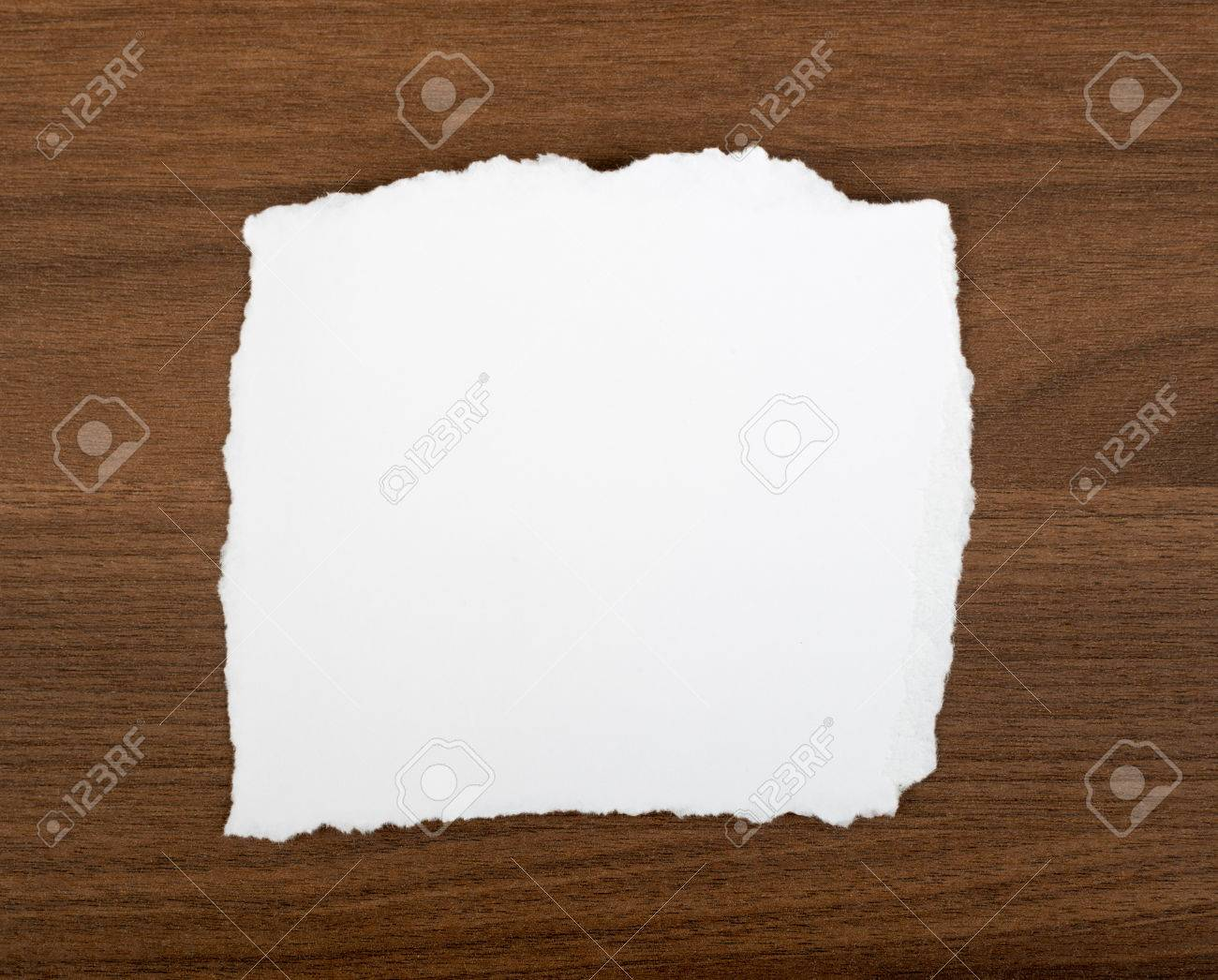 white blank piece of paper with uneven edges on brown wood table