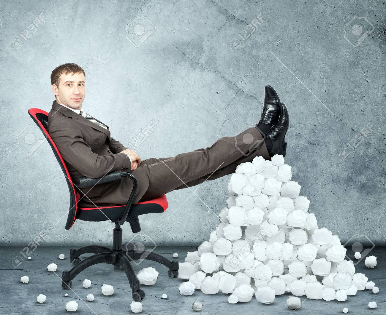 businessman sitting on chair and pile crumpled paper balls on