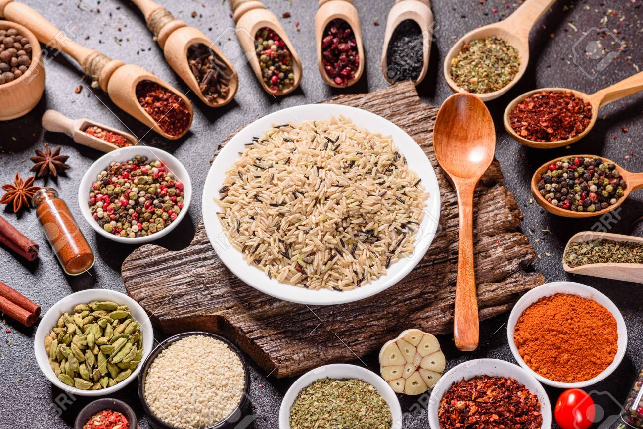 A set of spices and herbs. Indian cuisine. Pepper, salt, paprika, basil and other on a dark background. Top view. Free copy space - 138095396