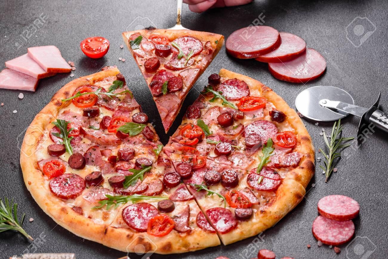 Pepperoni Pizza with Mozzarella cheese, salami, ham. Italian pizza on a dark background - 139334327