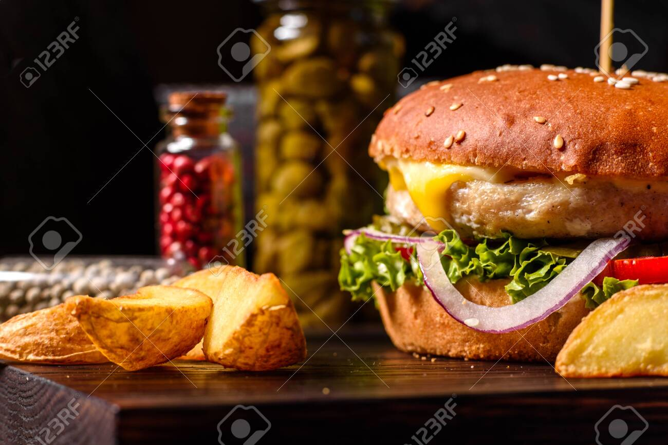 Home made hamburger with lettuce and cheese. Close-up of home made tasty burgers on wooden table - 152970293