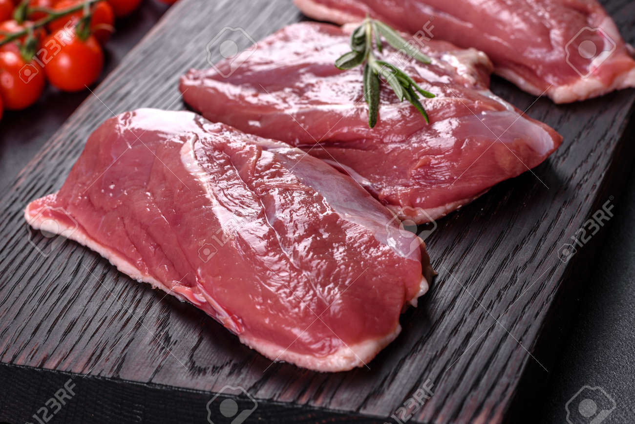 Raw duck with herbs and spices on a dark concrete background. Raw meat prepared for baking - 168132296