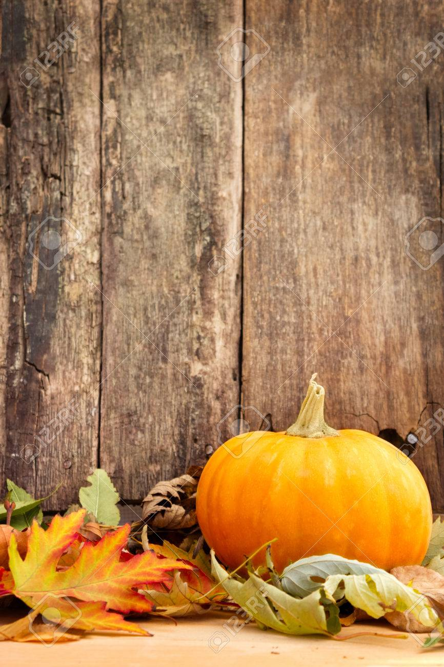 autumn leaves and pumpkin on wooden background - 23796552