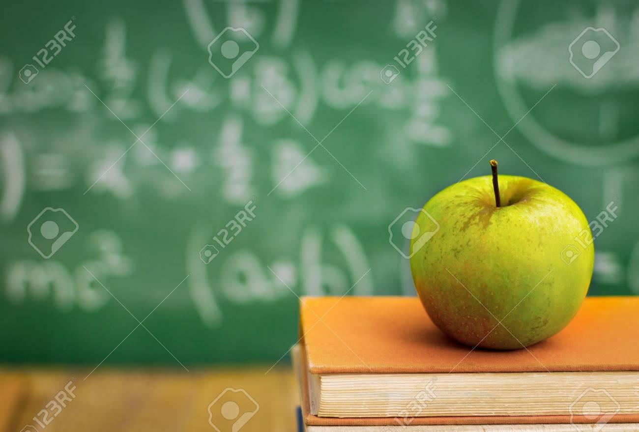 Apple on  school books over green  blackboard Standard-Bild - 33271959