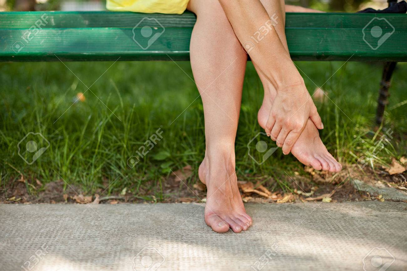 Girl sitting on bench and massaging tired legs Standard-Bild - 75318228